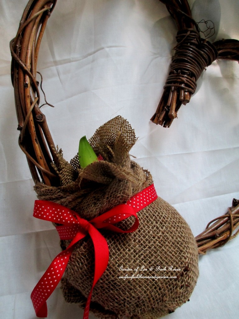 attach the burlap wrapped ball to the wreath with floral wire, then add a ribbon https://ourfairfieldhomeandgarden.com/diy-amaryllis-heart-wreath/