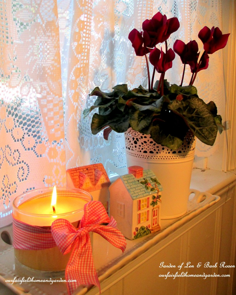 cyclamen, tiny salt & pepper houses and a candle https://ourfairfieldhomeandgarden.com/be-my-valentine-valentine-decor/