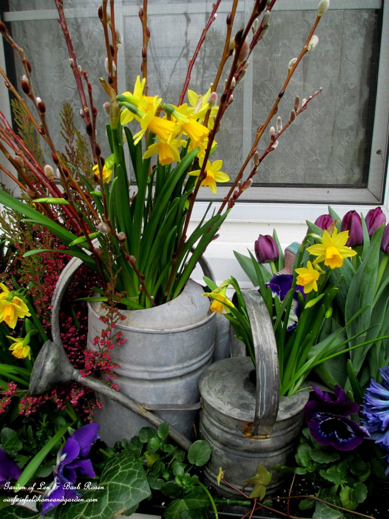 Close-up of the watering cans in the windowbox. https://ourfairfieldhomeandgarden.com/diy-project-welcome-spring-time-to-change-the-window-boxes/