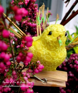 Yellow fabric bird accent sitting in the heather. https://ourfairfieldhomeandgarden.com/diy-project-welcome-spring-time-to-change-the-window-boxes/