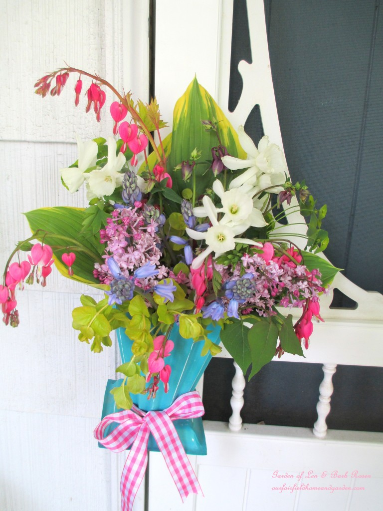 May Day Basket hung on the screen door handle. https://ourfairfieldhomeandgarden.com/diy-project-gather-flowers-for-a-may-day-basket/