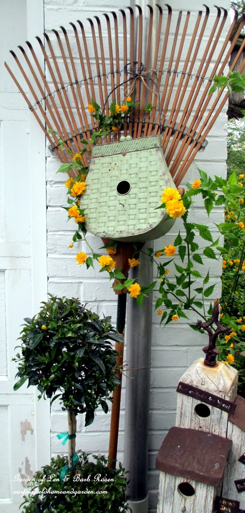Birdhouse rake by the garage https://ourfairfieldhomeandgarden.com/diy-project-repurposed-rakes/