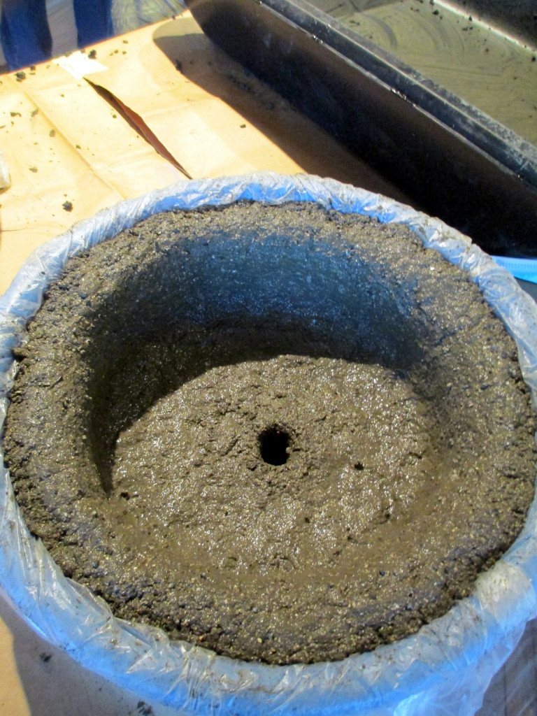 Step #  ~ Pat the wet hypertufa mixture firmly onto the bottom and sides of the container. Make a drainage hole in the bottom too!