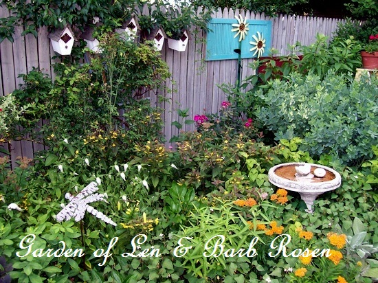 Birdhouses on a backfence http://ourfairfieldhomeandgarden.com/its-all-about-the-birds-birdfeeders-birdbaths-and-birdhouses-in-our-garden/