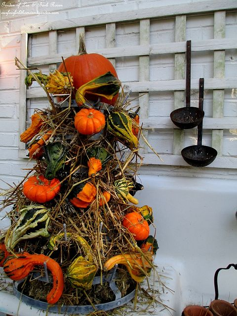 Gourd Tower ~ hay & gourds fill a metal bottle rack https://ourfairfieldhomeandgarden.com/autumn-garden-accents-inside-and-out/
