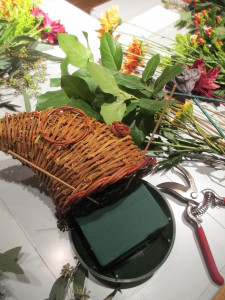Gather the materials and remember to start at the base with greens to cover the oasis, then add accent pieces & flowers.