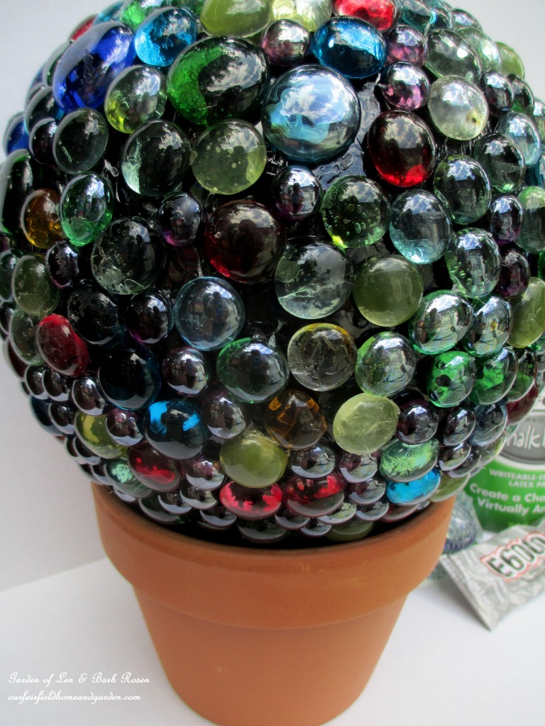 Use the flower pot as a base as you glue! https://ourfairfieldhomeandgarden.com/diy-project-bowling-ball-garden-accent/