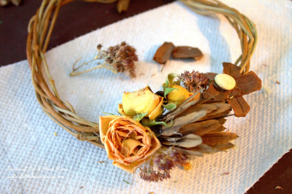 Hot glue was used to attach dried materials to a small wreath. https://ourfairfieldhomeandgarden.com/diy-spring-wreaths/