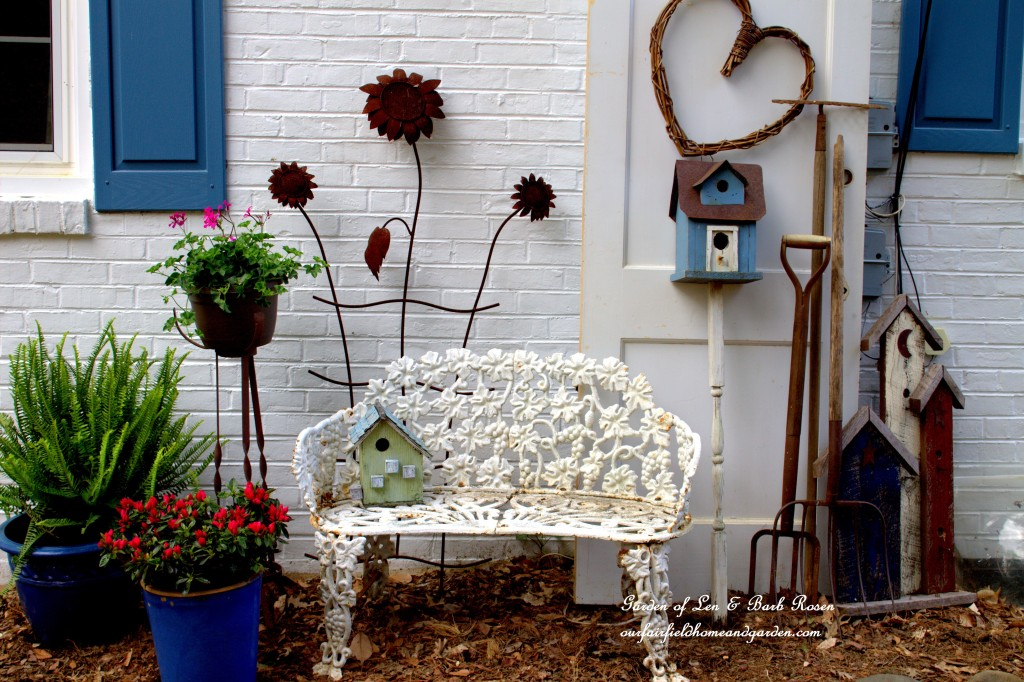 A Country Garden vignette covers the utility boxes! https://ourfairfieldhomeandgarden.com/curb-appeal-hiding-an-eyesore-in-the-garden/