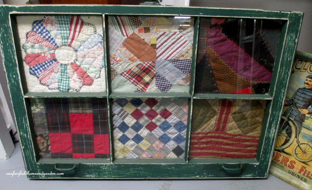 Quilt scraps framed in an old window https://ourfairfieldhomeandgarden.com/recycled-window-picture-frame/