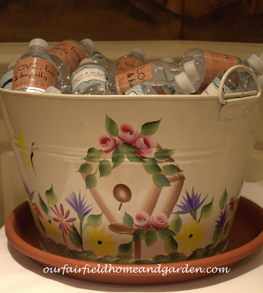 Handpainted Water Bottle Bucket http://ourfairfieldhomeandgarden.com/loving-touches-create-an-elegant-wedding-for-less/