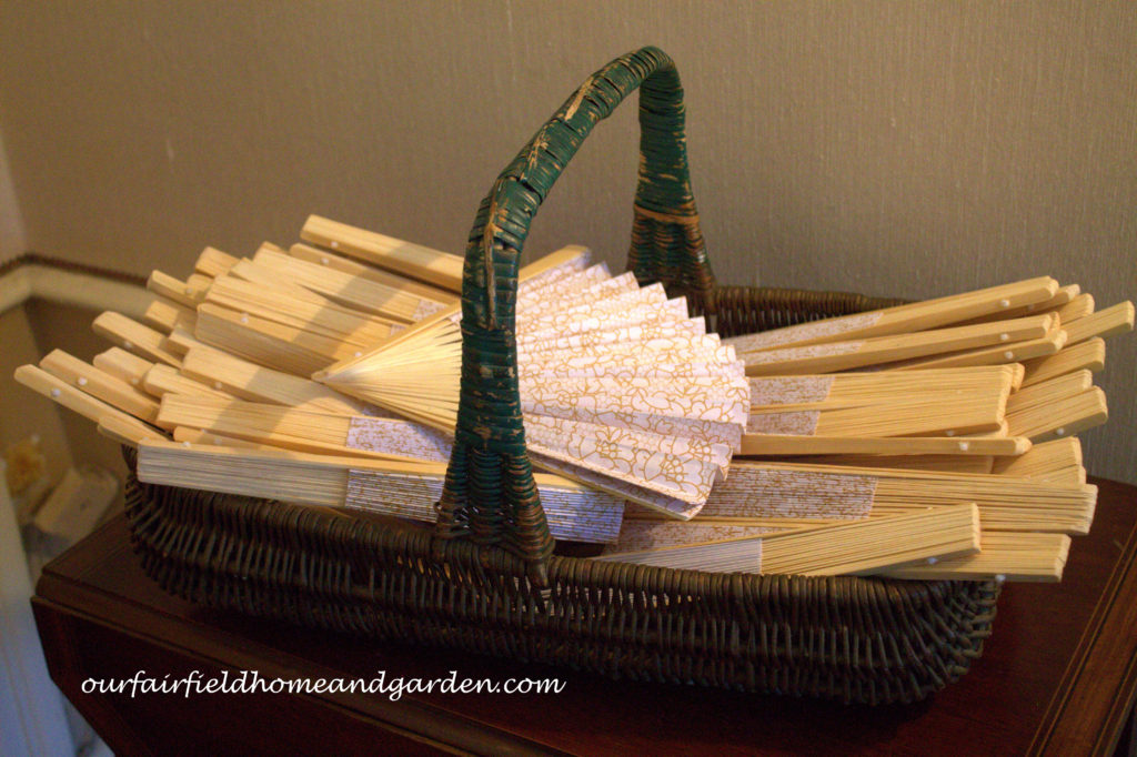 Paper fans in a vintage basket https://ourfairfieldhomeandgarden.com/loving-touches-create-an-elegant-wedding-for-less/